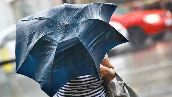 強い風雨で変形した傘をさして歩く人