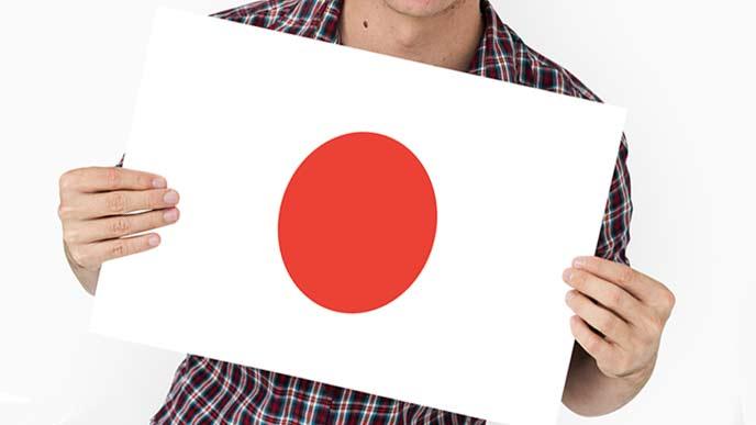 日本国旗を持つ男性