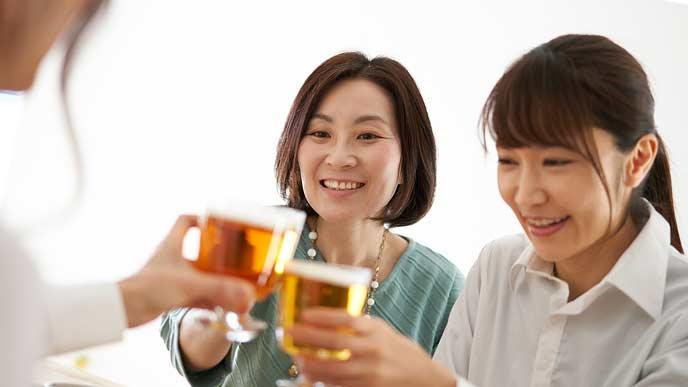 飲み会でグラスで乾杯をする女子社員