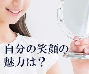 鏡で自分の笑顔を見る女性