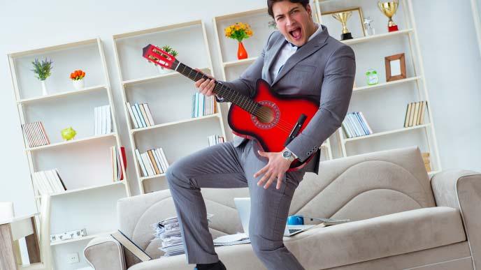 ギターを弾きまくるスーツ姿の男性