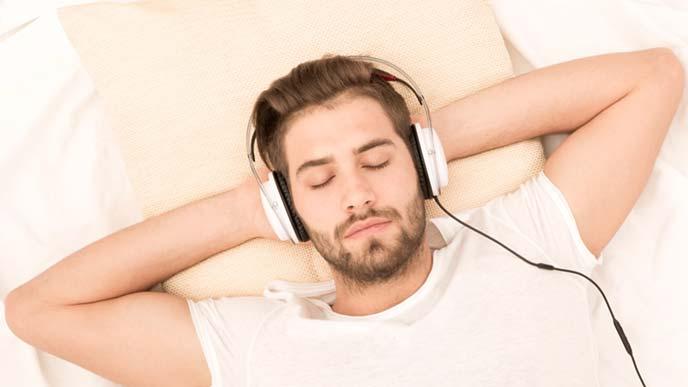 ヘッドフォンをかけ横たわる男性