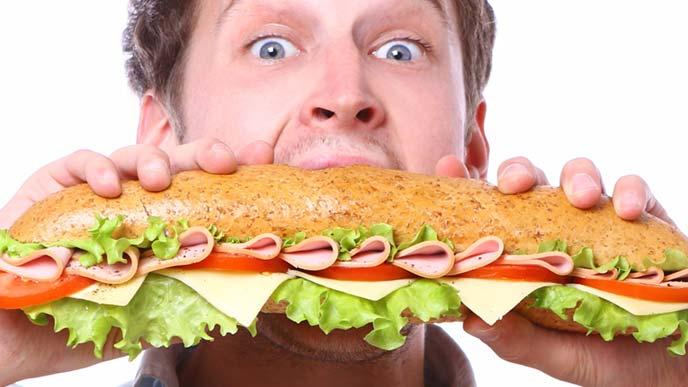 大きなサブマリンサンドに食らいつく男性
