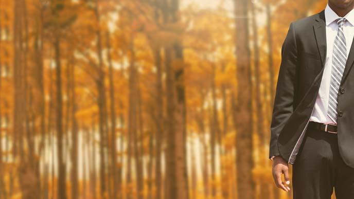 秋の林に立つスーツ姿の男性