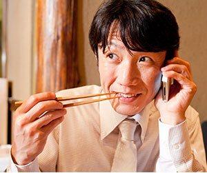 飲み会で電話で話しながら食べる男性