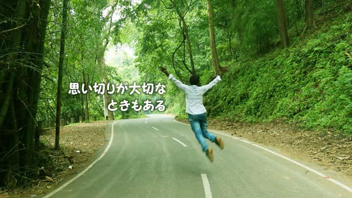 山の中の舗装道路でジャンプする人の後ろ姿