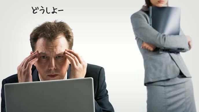 ノートパソコンの前で頭を抱える男性と後ろから見つめる女性