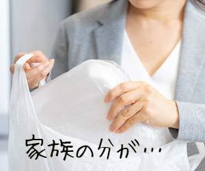レジ袋から大きなトレー食品を取り出す女性