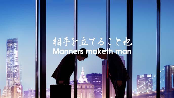 ビルの谷間をバックにお辞儀を交わす日本のビジネスマン2人