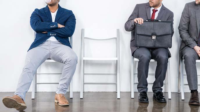 ガムを噛みながら不躾な姿勢で足を延ばす男性と嫌がるビジネスマン2名