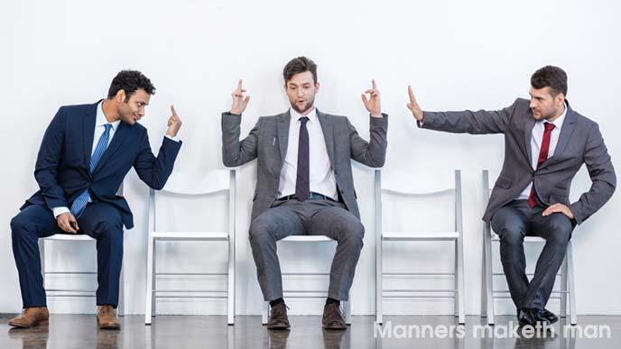 仲違をする多民族のビジネスマン2人と間に挟まれる男性