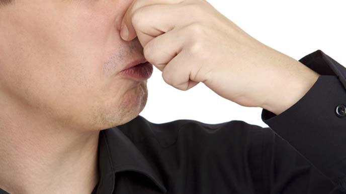 鼻をつまんで息を止める男性