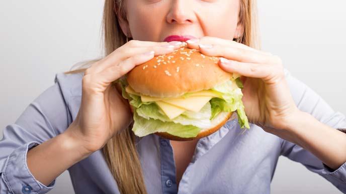 サンドイッチに食らいつく女性