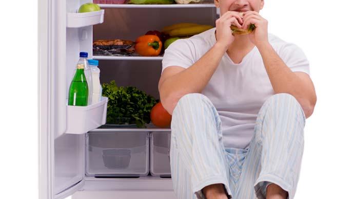 開けっぱなしの冷蔵庫の前で何やら食べている男性