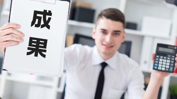 電卓を手に成果を掲げるスーツ姿の男子学生