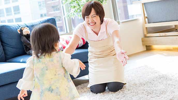歩み寄る幼児に両腕を広げる笑顔の保育士