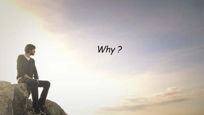 薄暮の荒野で岩に腰掛け遠くを見つめる青年
