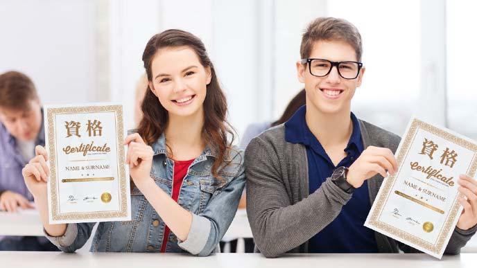 資格証を手に微笑む若い男女