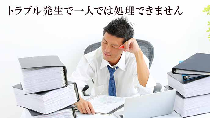 机の上の大量のファイルに辟易する会社員