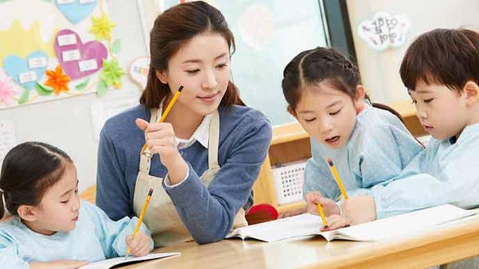 園児に勉強指導する幼稚園教諭