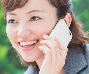 お礼の電話をする女性