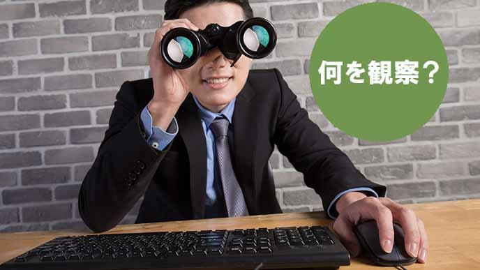 双眼鏡を覗き込むビジネスマン