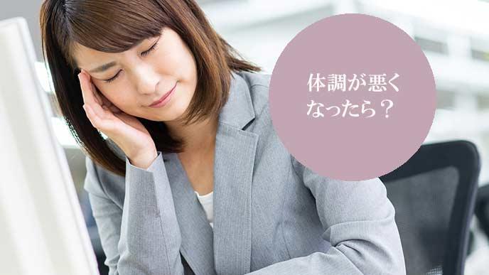 会社のデスクで、こめかみを指で押さえて疲れた表情の女性