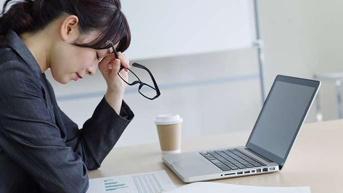 職場のデスクで悩む女性