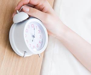 目覚まし時計を止める女性の手