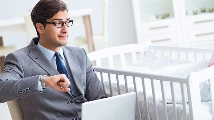 自宅で赤ちゃんの様子を見ながら腕時計を確認する男性