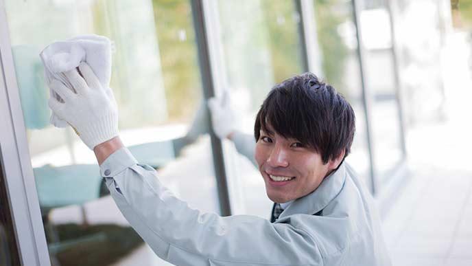 窓ガラスの掃除をする男性