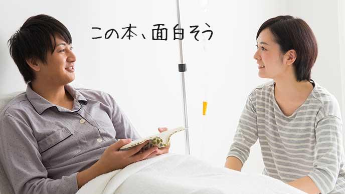 病院のベッドで文庫本を手にする男性とお見舞いの女性