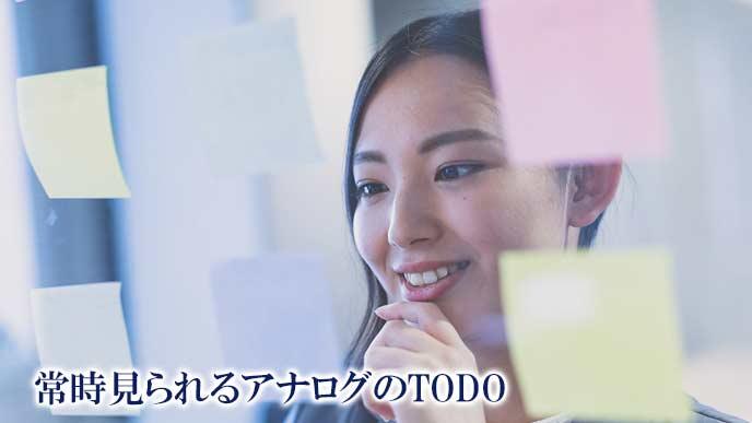 メモ付箋を透明ボードに貼って整理する女性社員