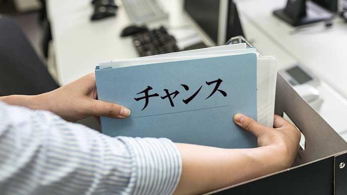箱にファイルを仕舞う社員とチャンスの文字